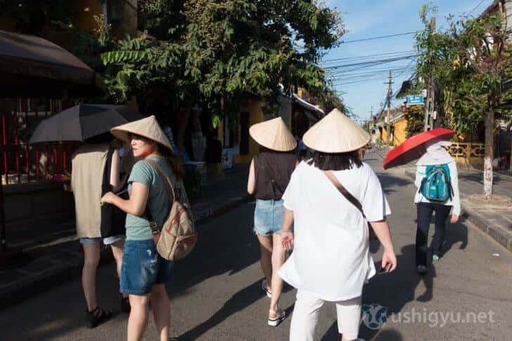 ホイアンにいる傘をかぶった観光客